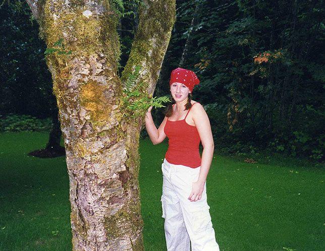 Photo of Ali standing next to tree